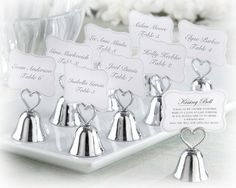 """Happiness is like a kiss. It feels best when you give it to someone else."" On the day you marry your ""someone else,"" celebrate all the smooches to come with the ""Kissing Bell"" Place Card/Photo Holder wedding favor. Fun for your guests—and lots of fun for ""you!"" Features and facts:    Sweet, silver-finish metal bell place card/photo holder with braided, openwork heart handle  Bell measures 1 ¾"" h x 1 ¼ "" in diameter  Coordinating place cards included. #weddingfavors"