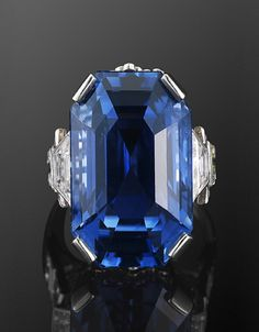 28.83ct Natural Ceylon Sapphire and Diamond Ring An emerald cut Ceylon sapphire weighing approximately 28.83 carats is set in a geometric diamond platinum mounting with a total of approximately 1.90 carats of diamonds.