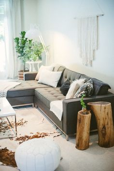 dark grey sectional + wood stump side tables
