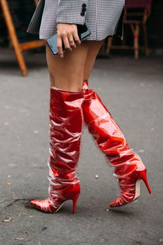 Attendees at Paris Fashion Week Fall 2018 - Street Fashion, killer red patent leather knee high boots, red knee high boots with pointy toes and stilettos, red boots with clear plastic layer on them,