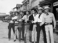 """Photo of all the Warner Brothers Studio television western stars who had programs on ABC. From left: Will Hutchins (""""Sugarfoot"""" Brewster-Sugarfoot), Peter Brown (Johnny McKay-Lawman), Jack Kelly (Bart Maverick-Maverick), Ty Hardin (Bronco Laine-Bronco), James Garner (Bret Maverick-Maverick), Wayde Preston (Christopher Colt-Colt .45), John Russell (Dan Troop-Lawman)."""