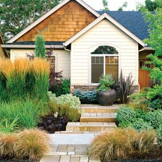 Rusty-hued Carex testacea softens the front path, while green kniphofia, plum Heuchera 'Obsidian', Libertia peregrinans 'Bronze Sword', and euphorbia surround the 'Karl Foerster' gras Low Water Landscaping, Front Yard Landscaping, Landscaping Ideas, Colorado Landscaping, Inexpensive Landscaping, Hillside Landscaping, Luxury Landscaping, Front Gardens, Outdoor Gardens