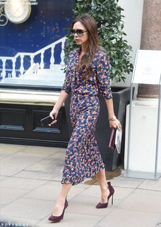 Victoria Beckham in a floral dress and matching heels.