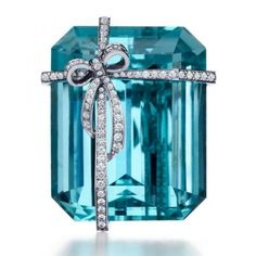 A brooch from Tiffany and Co. with an emerald-cut aquamarine accented with a diamond-and-platinum bow. shrtsht3