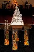 Wedding Cake display- glass cake table with illuminated floral filled cylinder vases for legs Wedding Cake Display, Wedding Cake Stands, Unique Wedding Cakes, Wedding Tables, Cake Table, Dessert Table, Cylinder Vase, Vases, Wedding Decorations