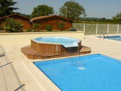 Jacuzzi avec contour composée de lame de bois. On remarque un versement dans une piscine extérieure peu profonde.