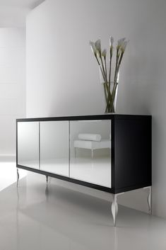 The Luxury Mirrored Sideboard at Juliettes Interiors is a truly stunning statement for any room in the house. Striking in any setting, the ultimate in a stylish and glamorous storage solution. As comfortable in a dining room, bedroom or study as it is as a welcome in an entrance hallway. Shown here with 3 bevelled mirrored glass doors with push open mechanisms to enhance the minimal look and feel, together with a matt black lacquered frame and finally completed with polished steel baroque…