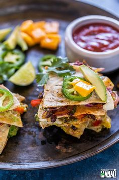 Vegetarian Quesadillas filled with spicy black bean filling and mango avocado salsa! Bursting with summer flavors and gets ready in no time. Gluten-free. Find the recipe on www.cookwithmanali.com