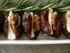 Dates stuffed with cream cheese and a walnut and garnished with a rosemary sprigs. So yummy!
