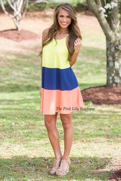 You are sure to be in the middle of the spotlight wherever you wear this little number! Chic and vibrant, it's the perfect dress for the new season! It features a colorblock style in navy, yellow, and neon coral for a bright summery pop of color, paired with spaghetti straps and breathable fabric that will keep you cool!