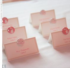 The Escort Cards    Buttons in pink and white lent a whimsical air to tented escort cards