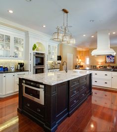 Traditional kitchen cabinetry with a passion for the old world #kitchenisland #whitecabinets #blackisland
