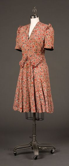 Dress 1941-42 - United States government implemented the L-85 regulations in 1942. L-85 dictated the styling of garments with an eye to conserving materials and production time. Skirt length, hem width and types of trim were strictly regulated.