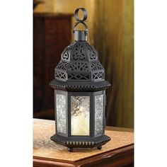 "Intricate cutout metalwork blazes with light as a candle sets this lantern aglow. A decorating treasure inspired by the mysteries of the fabled Far East! Material(s): IRON GLASS Dimensions: 4.5"" x 3.7"