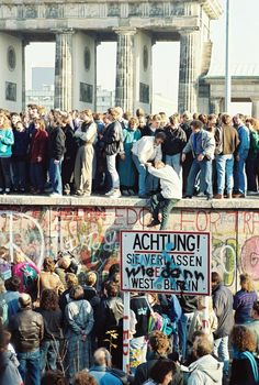 "English: People atop the Berlin Wall near the Brandenburg Gate on 09 November The text on the sign ""Achtung! You are now leaving West Berlin"") has been modified with an additional text ""Wie denn? Ddr Brd, German Reunification, Berlin Hauptstadt, Historia Universal, Brandenburg Gate, Marie Curie, East Germany, Germany Berlin, Interesting History"