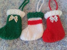 Pack of 3 Tree Decorations. This item is hand knitted in a smoke and pet free environment in quality acrylic yarn which is machine washable. Each set comprises of a red sock with a white top, a green sock with a white top and a white sock with a red stripe and green top. They …