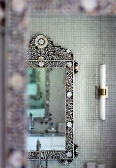 nice juxtapositions:  ornate Moroccan mother-of-pearl mirror against sea glass mosaic tile + modern sconces