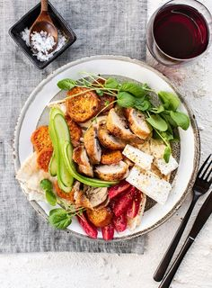 Roast chicken thighs are served with sweet potatoes, greens and hummus for an easy midweek meal.