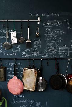 Verf een muur met krijtbordverf, schrijf er iets op (bijvoorbeeld je favoriete recept of een boodschappenlijstje) en hang je pannen aan de muur.