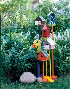 Cute wire stand & cluster of 6 colorful birdhouses with varying height to encourage us into the garden.