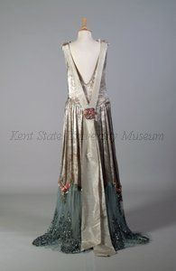 Boué Soeurs couture evening dress Paris, France in robe de style from 1928 made from brocaded silver lame, pale blue net embroidered with silk floral trim, ribbon work flowers, bugle glass beads and sequins with chemise sleeveless style, dropped waist, gathered skirt cut away in front and with ruffle of pale blue net trim at the hem.