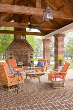 Architectural elements unite this covered patio to the home, as do the ceiling fan, chandeliers, upholstered furniture and fireplace. Brick and wood keep it tied to nature. More beautiful outdoor spaces: http://www.midwestliving.com/garden/ideas/30-beautiful-backyards/page/9/0