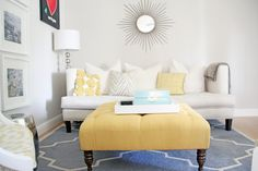 Grey and yellow living room with sunburst mirror and padded ottoman
