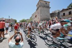 The pack passes medieval fortifications in Pezenas during the seventh stage of the Tour de France. (Christophe Ena/AP)