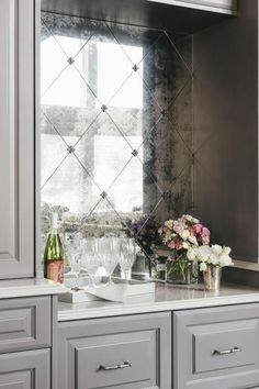cuisine équipée moderne, amenagement cuisine, miroir vintage effet vieilli, coin décoré avec bouteille de vin, deux verres et des fleurs en blanc et rose, plan de travail blanc