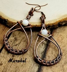 A perfect pair of earrings for the beach. Copper wire is woven and formed into a teardrop shape. Wires crossover at the top of the teardrop forming a small frame for the shell bead. Wire is oxidized and polished. White shell bead is wired at the top of the teardrop. Teardrop is about 1 7/8