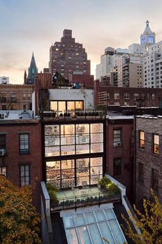 "Townhouse renovation.   ""The bricks-and-mortar rear wall of the two main floors has vanished, replaced by a glass curtain fitted with tiny diodes, invisible by day but glinting at night like a private constellation."""