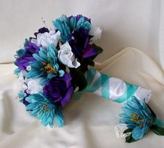 teal, purple, white rose, center a sunflower. bridesmaids in alternating dresses with one single sunflower.