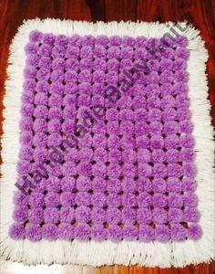 Purple pom pom blanket with white base and tassles.