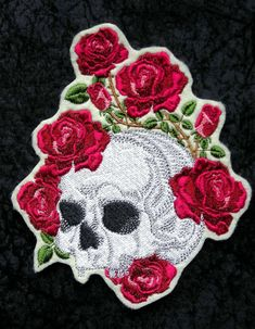 This Day of the Dead sugar skull iron on patch is surrounded by beautiful roses. They remind me of the old fashion thorny roses - very realistic looking and a really beautiful patch. The roses are done in two shades of red with pink highlights Color shades may vary. Its embroidered on off white premium felt using Sulky and RA rayon threads for excellent durability. Colors may vary slightly. The iron on patch measures approx. 5 inches wide by 6 high and takes about 90 minutes to stitch out…