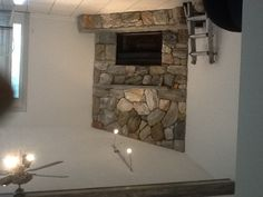Faux Rocks Rock Fireplace with faux driftwood beam