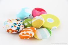make custom fabric-covered buttons without a kit or gadget by covering plain buttons with fabric scraps cut & stitched like a yo-yo.