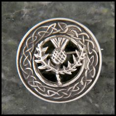 Mary's Thistle brooch is an original design by Walker Metalsmiths inspired by Irish and Scottish celtic traditions. This circular brooch features a central stylized thistle as a symbol of Scottish her