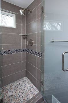 Grey porcelain tile was chosen for the floor, shower walls and wall behind the vanity. A unique stone and glass accent tile runs through the shower and vanity wall.