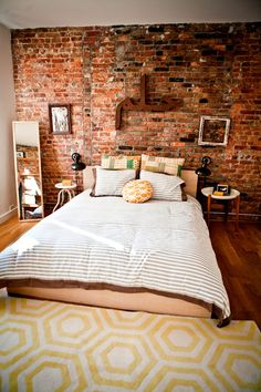 Bedroom. Yellow, warm tones. Exposed brick. Cozy.
