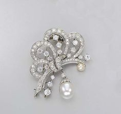 A DIAMOND AND SOUTH SEA CULTURED PEARL CLIP BROOCH    Designed as circular and old-cut diamond ribbons enhanced by a button-shaped cultured pearl, suspending a drop-shaped cultured pearl measuring approximately 12.60 x 14.10 mm. with diamond-set cap and collet surmount, mounted in platinum and 14k white gold (detachable), 6.0 cm.