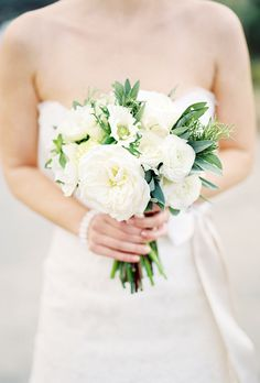 """Brides.com: All-White Wedding Bouquets. A Rustic Bouquet Accented with Fresh Herbs. Floral designer Holly Vesecky, of Hollyflora in Los Angeles, designed this posy for a bride getting married on a mountaintop vineyard, """"though the design is fairly universal,"""" she says. She used white peonies, garden roses, lysimachia, anemones, and ranunculus to create an informal arrangement accented with green herbs (sage, rosemary, and oregano—yum!).  See more rustic wedding flower ideas."""