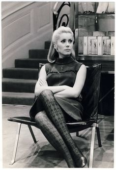 An incredible portrait by Giancarlo Botti of Catherine Deneuve, the muse of Yves Saint Laurent and the face of Chanel No. 5, seated on Poul Kjaerholm's iconic PK 22 leather lounge chair in the YSL showroom.