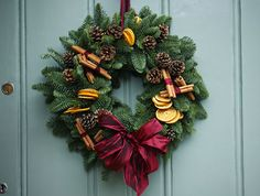 Evergreens, dried citrus slices, cones, and cinnamon sticks, wired scarlet ribbon.