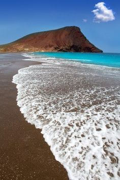 Beach Playa de la Tejita turquoise in Tenerife Canary islands with red mountain