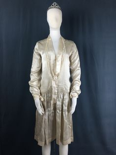 This silk wedding dress is from 1927 and has an opalescent beaded ribbon hanging from the neck.