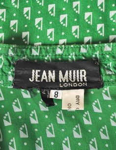"""Jean Muir Vintage Green Geometric Button Up Tunic Dress - Amarcord Vintage Fashion. Jean Muir London, 1970s, Green Geometric Button Up Tunic Dress - from Amarcord Vintage Fashion. """"Vivid green silk w/ grey geometric pattern throughout. Sitch details along collar, shoulders, and cuffs. Plastic button up front with matching fabric belt, lucite buckle. Pockets at hips. 100% silk."""" Priced at $795.00. Sold."""
