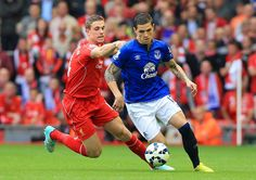 Liverpool's Jordan Henderson (left) is outflanked by Muhamed Besic in the 2014 Merseyside derby at Anfield