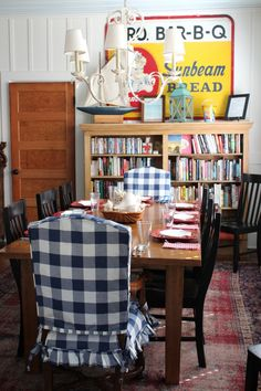 Mary Kay Andrews' beach house dining area with vintage grocery sign.  Love the buffalo check slipcovered chairs!