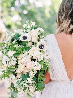Lush wedding bouquet with white Anemone. Greenery. Roses. Ranunculus.