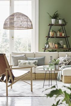 Modular seating with a woven base is the focal point in this relaxed green and white botanical living room. Terracotta, galvanised metal and green glass accessories complete the look. For more living room ideas visit housebeautiful.co.uk